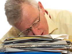 An exhausted senior businessman has fallen asleep on his work.